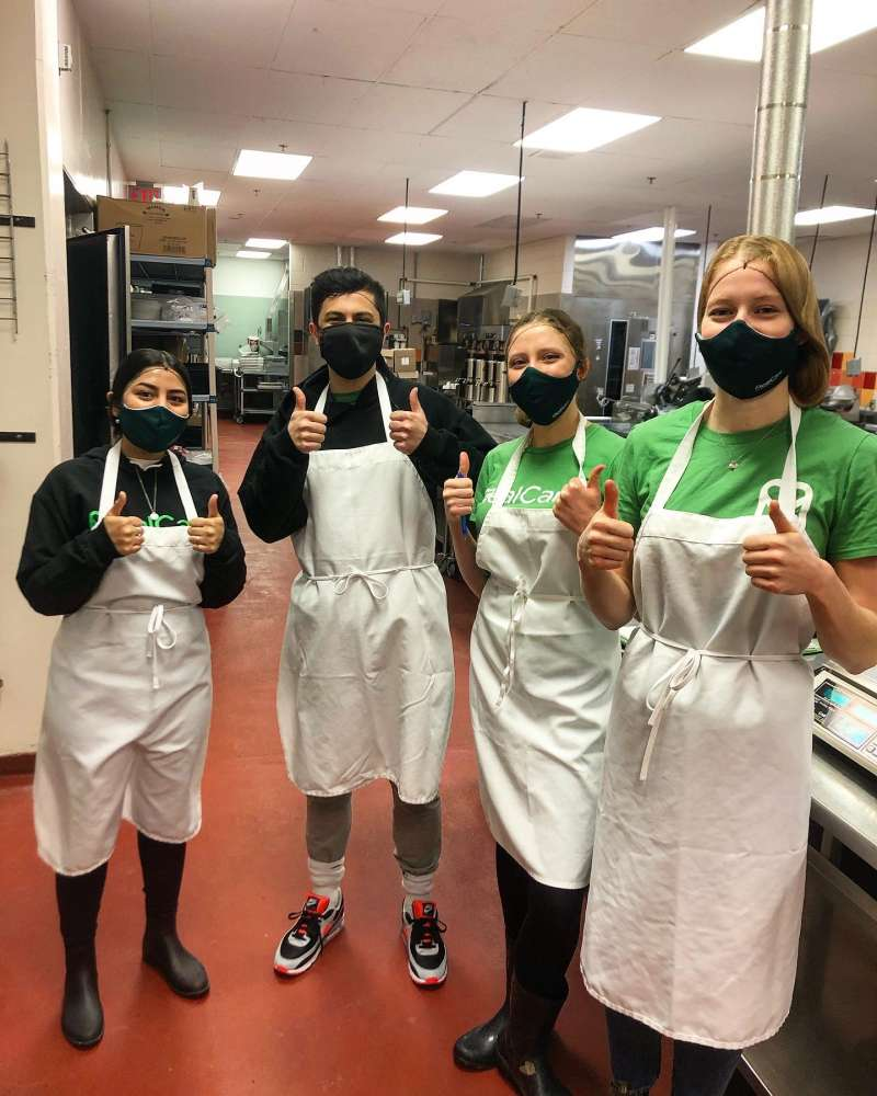 Four volunteers wearing aprons and masks give the thumbs up to the camera.