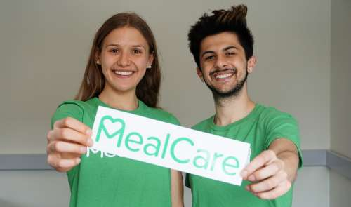A woman and a man wearing matching gree nshirts hold a sign that reads MealCare