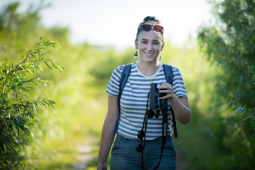 A photo of Danielle Nowasad carrying binoculars amid bushes and grass