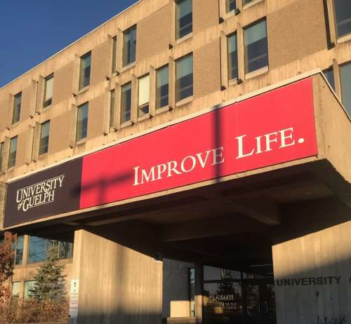 The University Centre on the U of G campus with a red sign that reads Improve Life