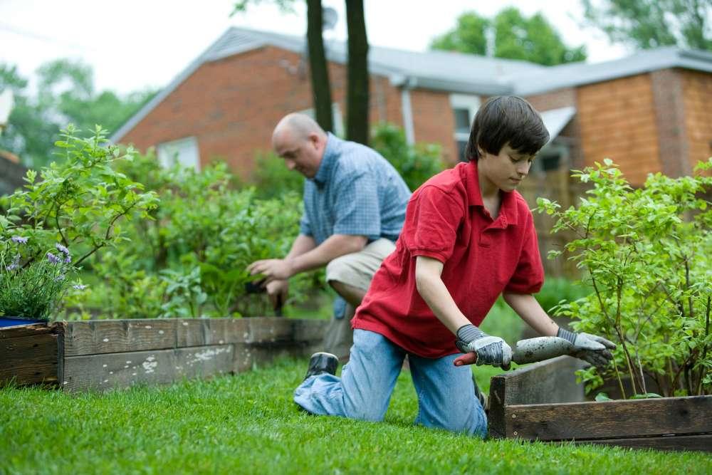 Two people kneel at raised garden beds