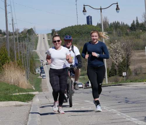 Two young women running along a highway, accompanied by man on bike.