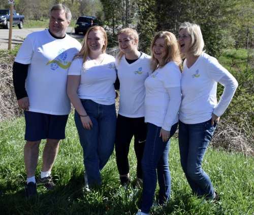 Five members of the same family, all smiling in the outdoors and wearing the same t-shirts.