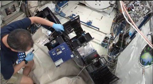 An astronaut on the ISS uses tools to place carrier on a transfer try