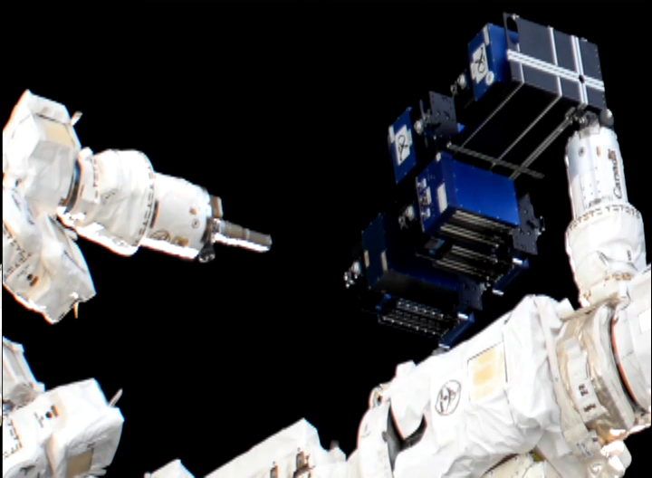 Robotic arms are shown transferring carriers onto the MISSE platform