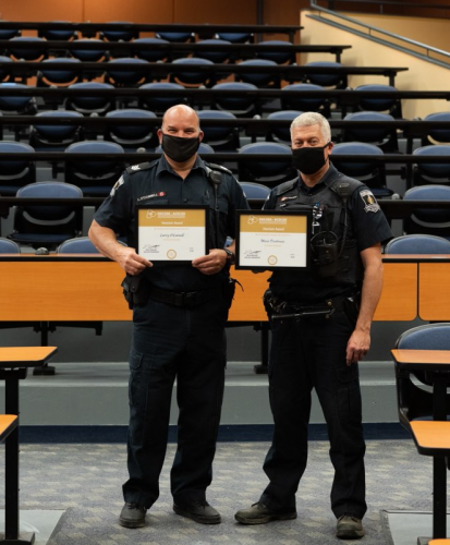 Two campus police officers holding heroism awards