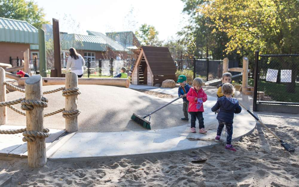 Children push brooms on a rubber sand-bridge in the CCLC playspace