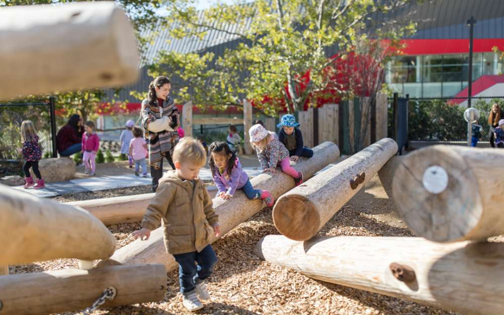 Children play on sloped log climbers
