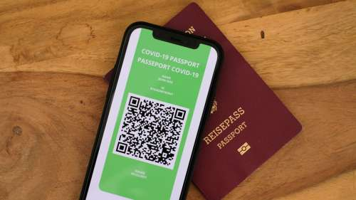 A cellphone with the words COVID-19 Passport on the screen sits on top of a German passport