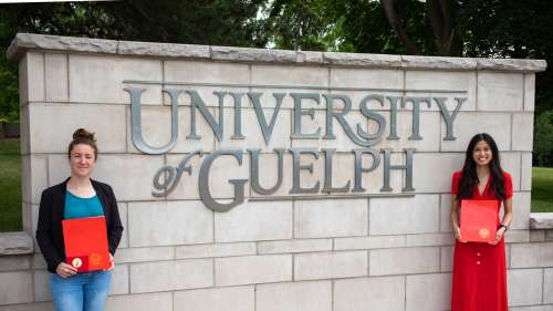 Claire Mindus and Anita Luu in front of the University of Guelph entrance sign