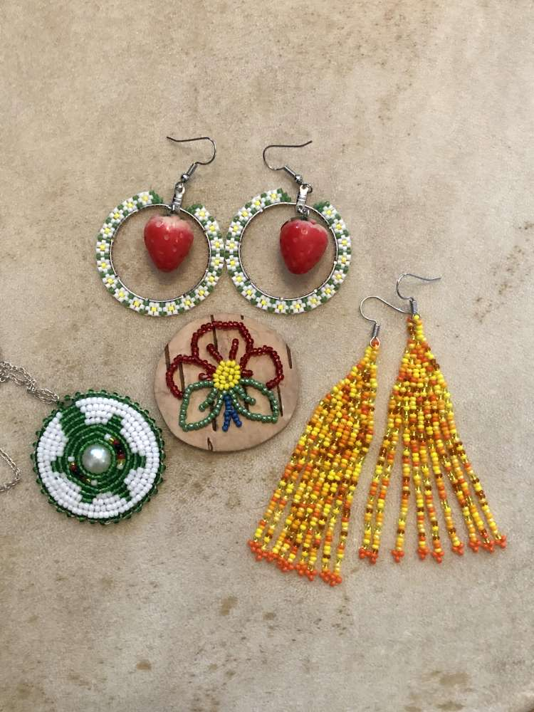 Two pairs of beaded earrings and 2 beaded pendants sit on a table