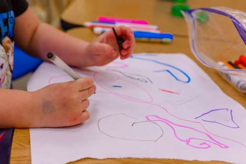 A child drawing with coloured markers on paper