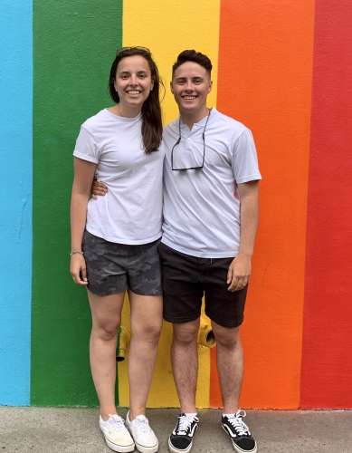 Young man and woman, Pride rainbow wall behind them