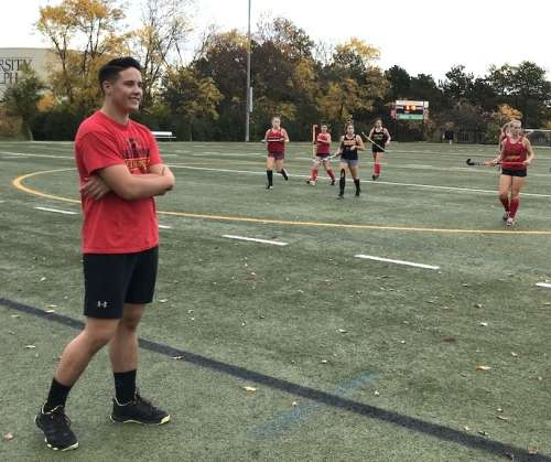 Young male coach with women's field hockey team