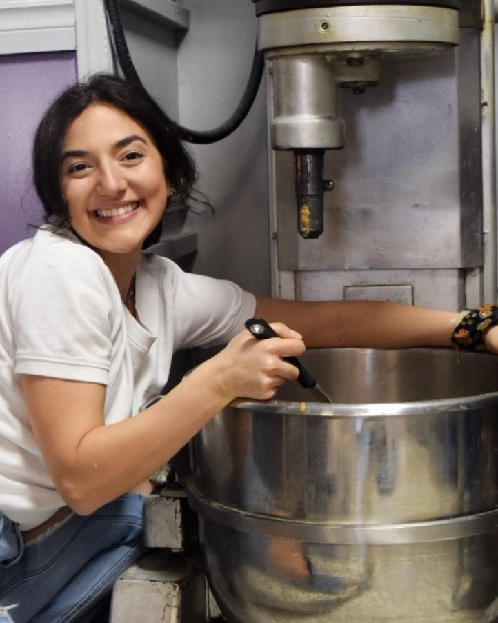 A woman sits beside a restaurant grade mixer