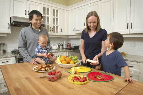 family with two young children around a kitchen counter with vegetables and fruit cut up on plates