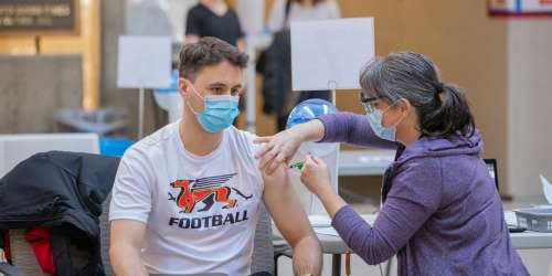 A person wearing Guelph Gryphon T-shirt gets a vaccine in the COVID-19 vaccination clinic in the University Centre on the U of G campus