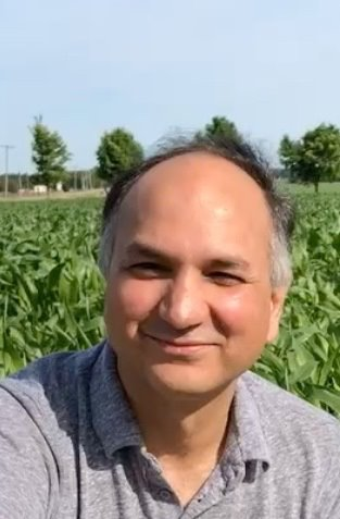 Dr. Manish Raizada from shoulders up with a corn filed in the background