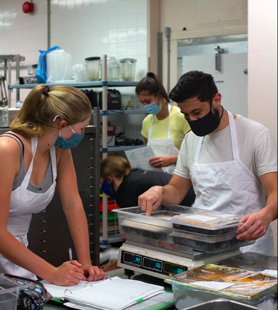 Four MealCare volunteers in a kitchen sort and weigh food containers