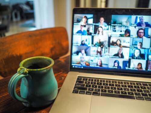 A ceramic mug sits beside a laptop with an online meeting on the screen