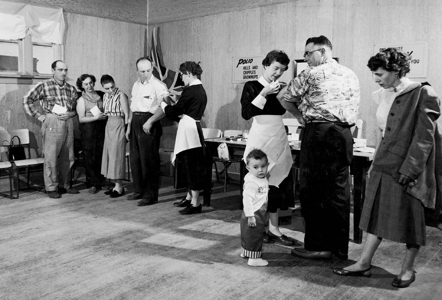 A black and white photo of . Two public health nurses vaccinating adults at a polio clinic.