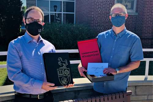 Brett Shepherd, director of Ridgetown campus with Dr. Simon Lachance, assistant dean of academic at Ridgetown campus, from the waist up. They are holding black and red boxes with the U of G logo on them. These are graduate boxes sent to all the graduates. There is a building the background.