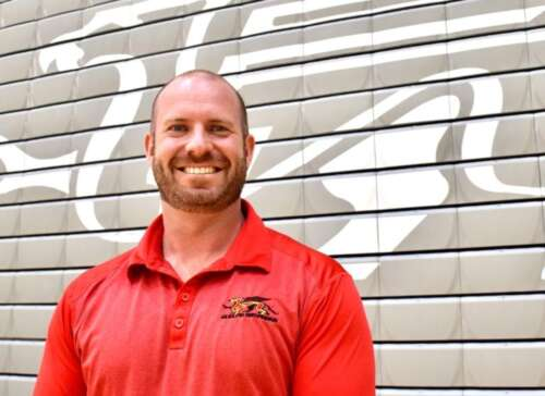Scott McRoberts standing in front of a wall with a white Gryphon logo. The image of his head and shoulders and he is wearing a red Gryphon shirt