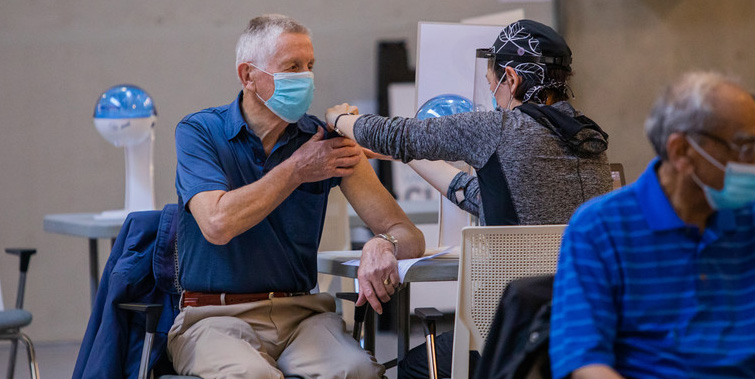 A man wearing a mask is given a needle at a vaccination clinic