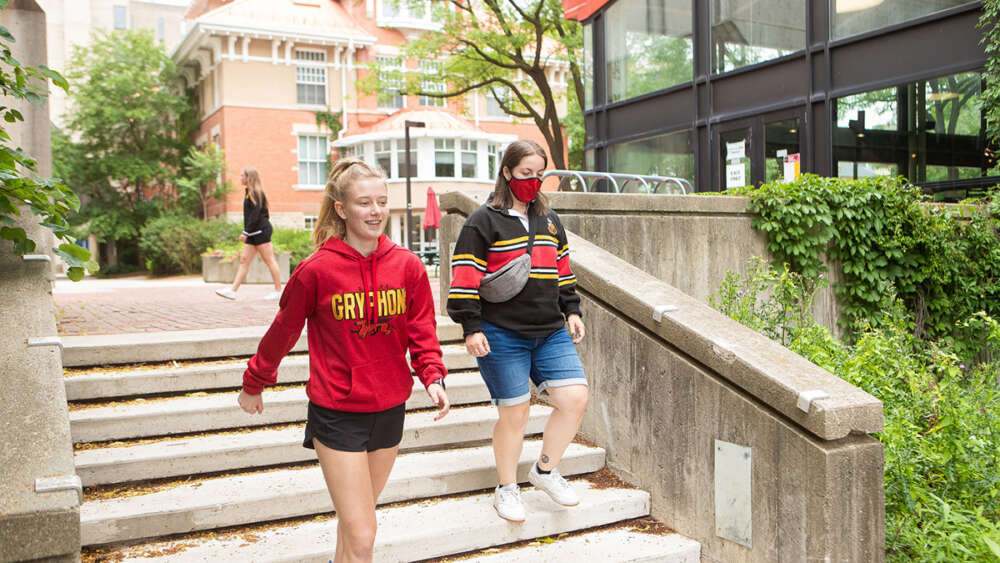 Two students wearing Gryphon sweaters walk down stairs on campus
