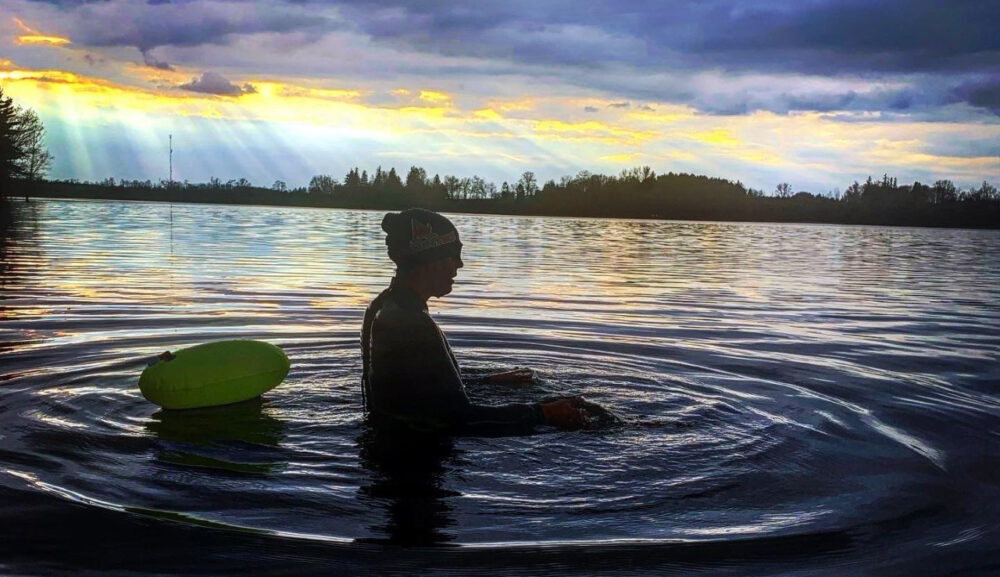 A silhouette of a woman in a swimcap in a lake with a sunset behind her