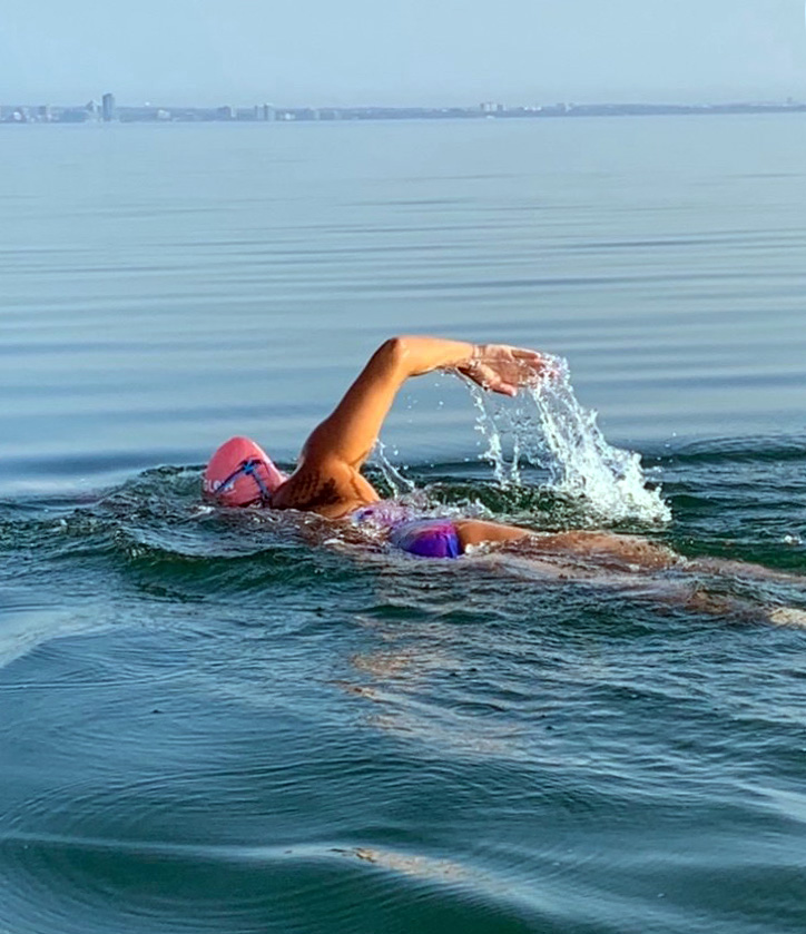 A woman is shown doing front crawl in a large lake
