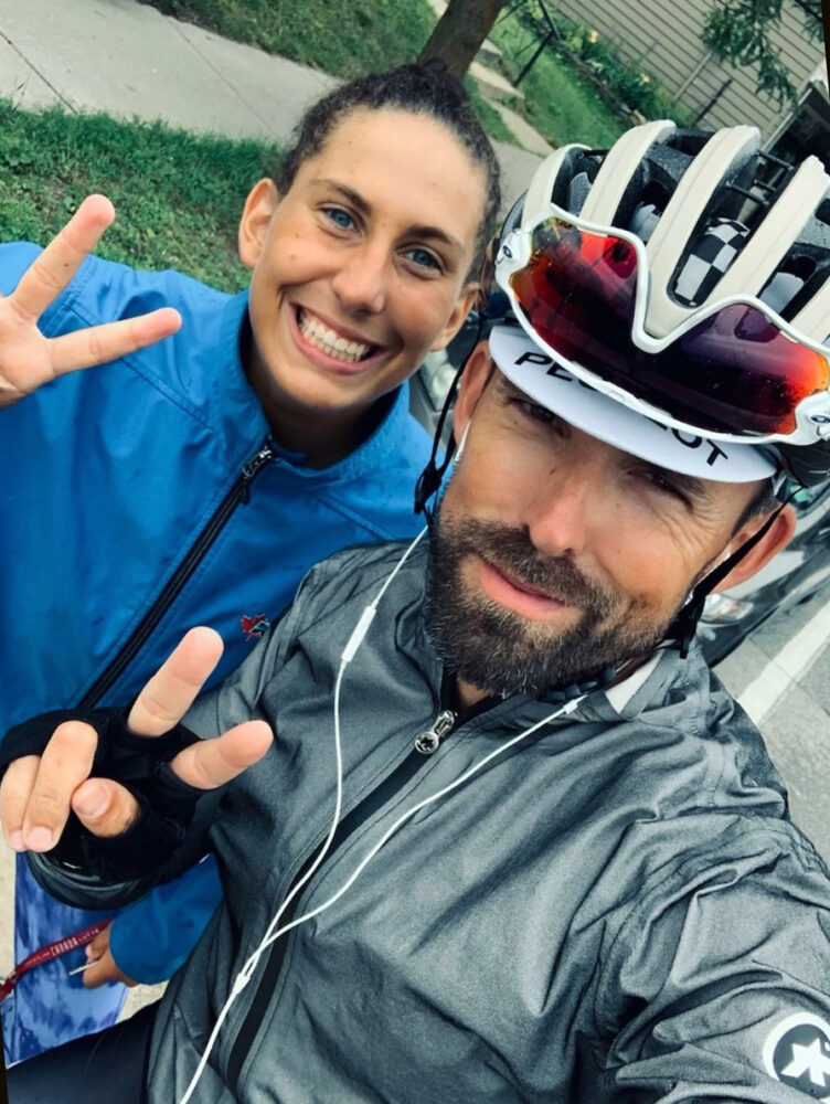 A woman and man give peace signs in a selfie
