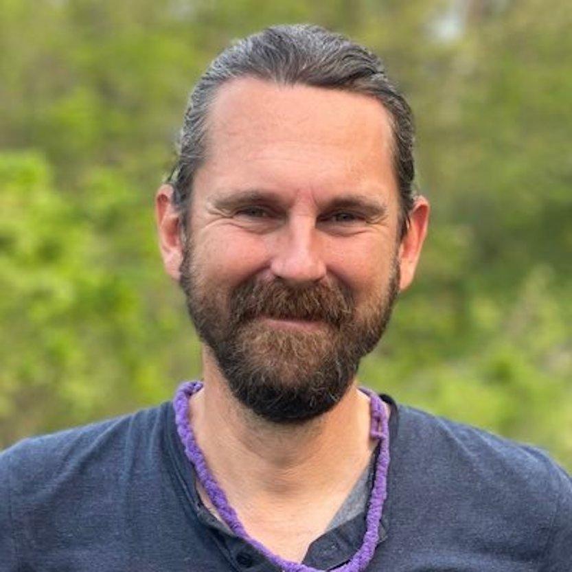 Bearded man wearing purple braided necklace