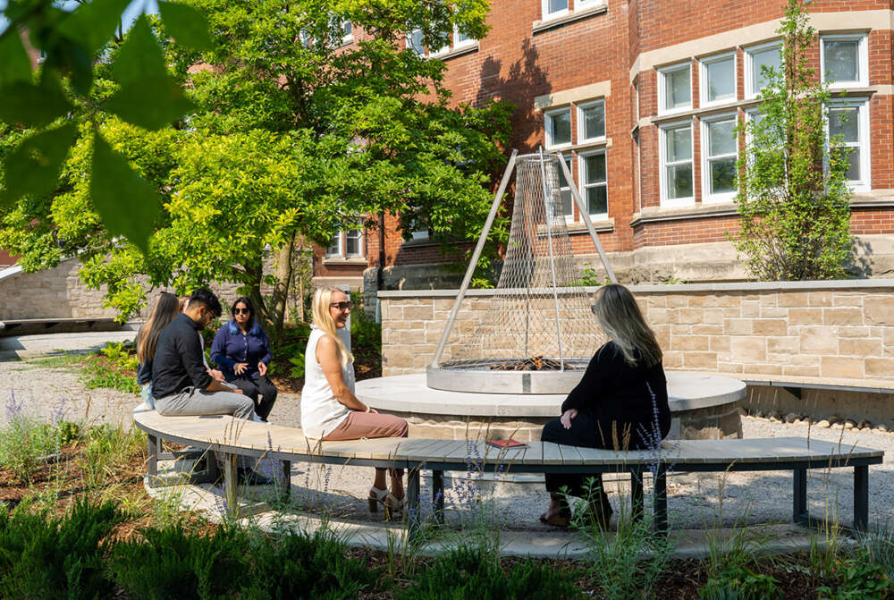 Students sit on a curved bench around a large fire table in the new Lang Plaza