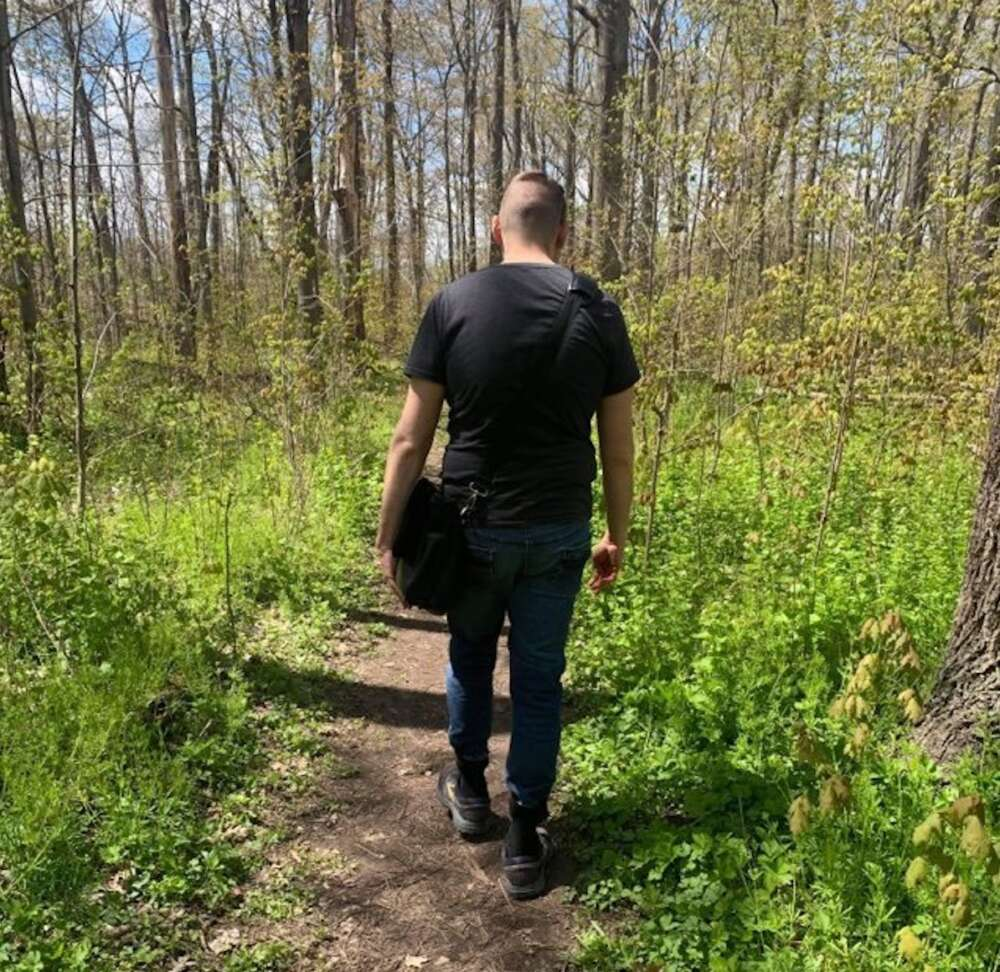 Young man walking away on wooded trail