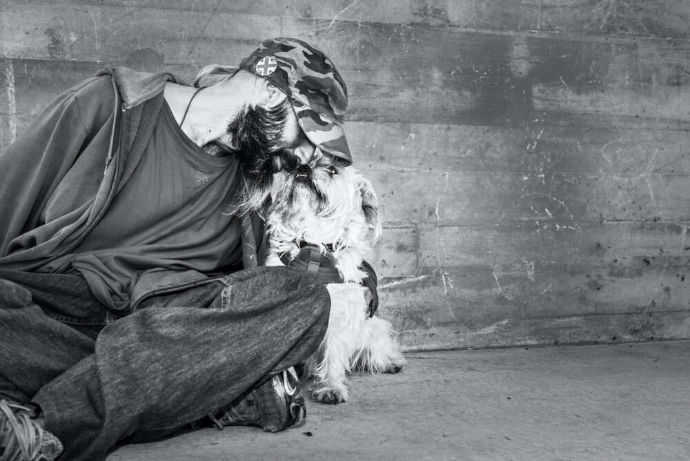 A man and his dog sitting against a concrete wall