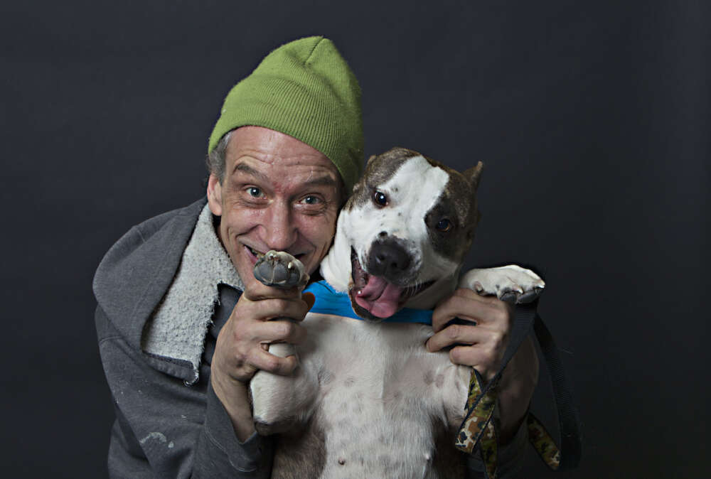 Man in green toque with smiling dog