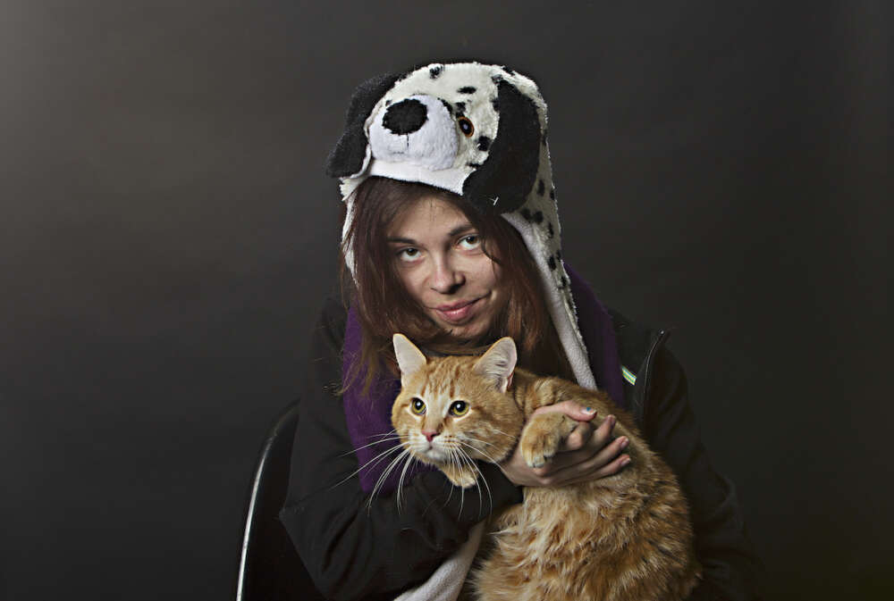 A woman in a dog cap holding her cat.