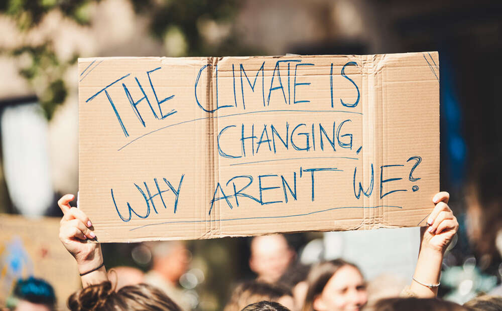 """A protest sign is held up that reads """"The climate is changing. Why aren't we?"""""""