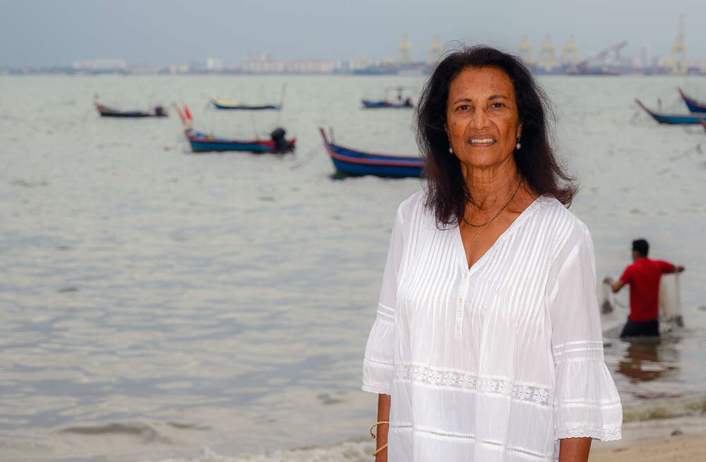 Dr. Shakuntala Haraksingh Thilsted stands on the beach near an Asian fishing port
