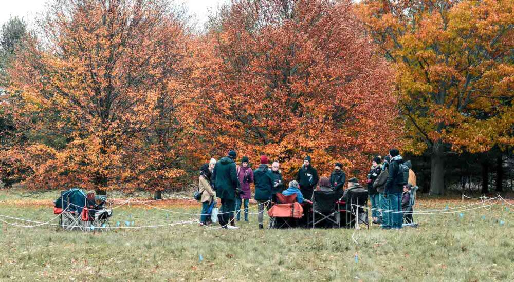 More than a dozen community members stand on an Arboretum field amid colourful autumn trees