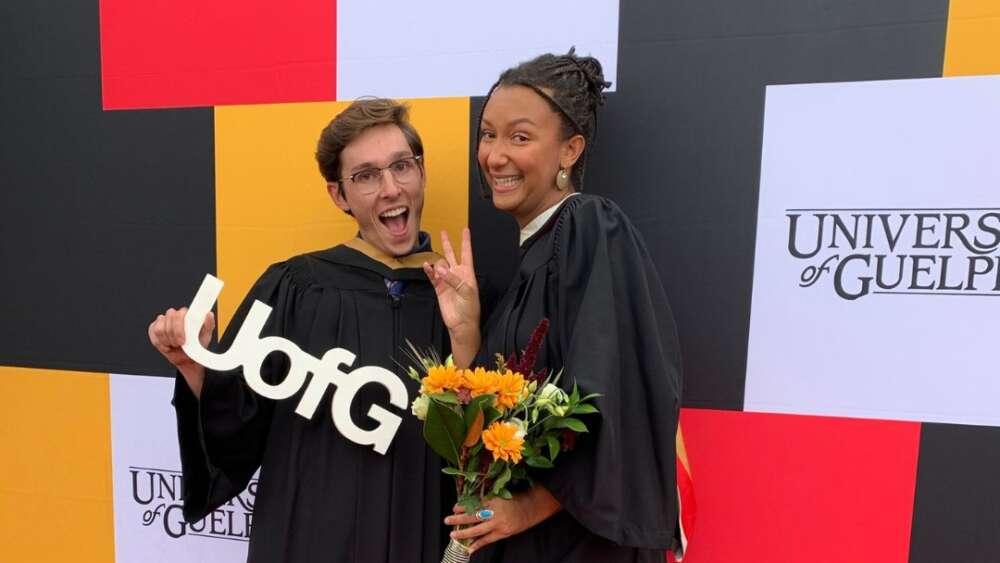Two graduates wearing regalia smile for the camera