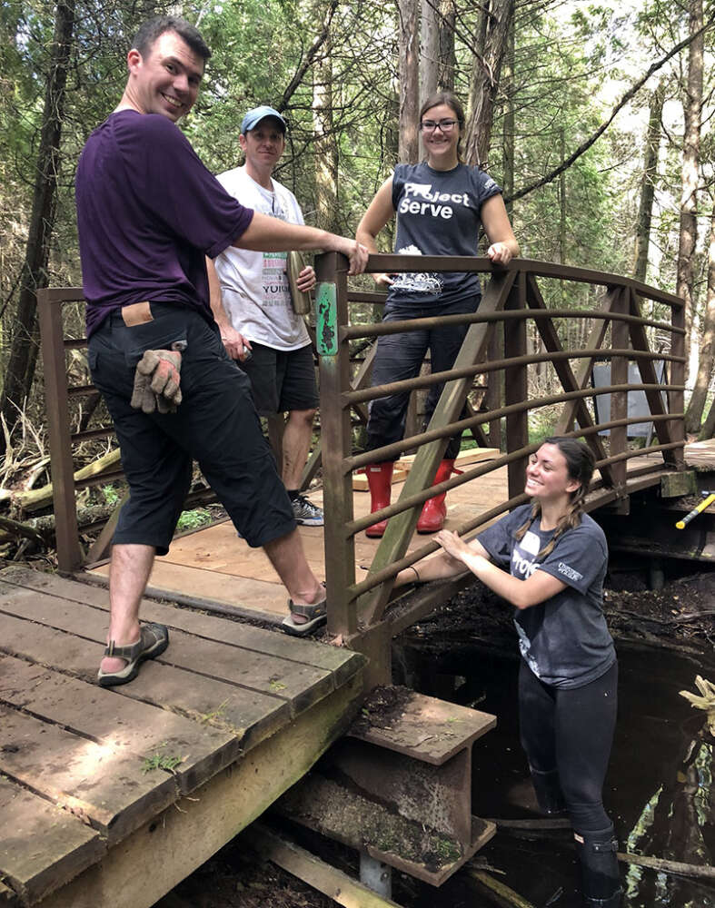 Four Project Serve volunteers stand near a bridge in a forest