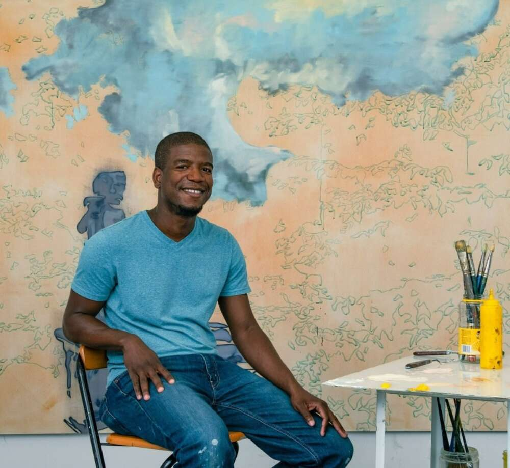 Plaskett award winner Emmanuel Osahor sits in front of a large canvas of his work