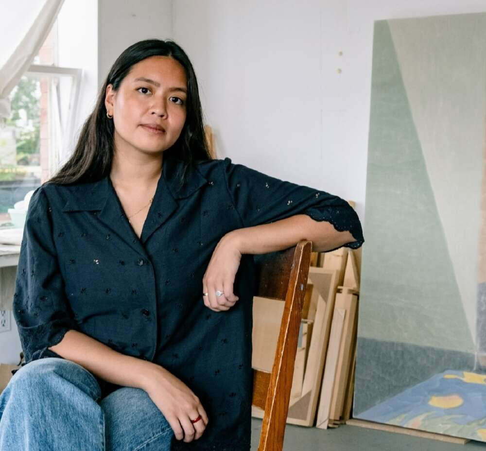 Painter Ella Gonzales sits on a wooden chair in her studio with several canvases behind her