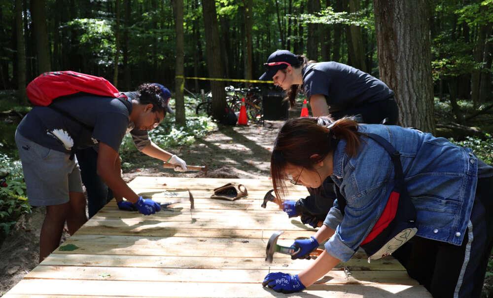 Three Project Serve volunteers hammer nails into boardwalks