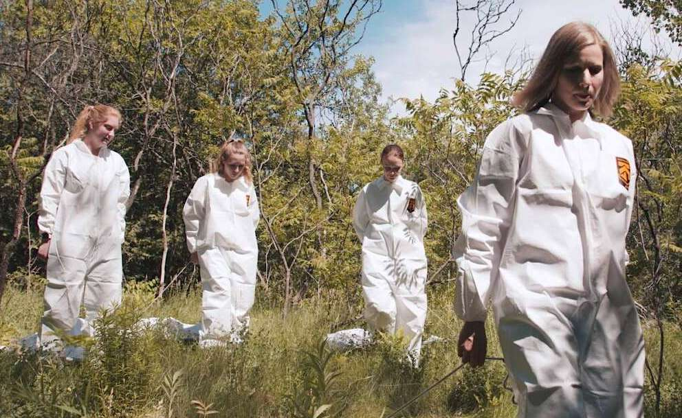 Four researchers in white suits in wooded setting