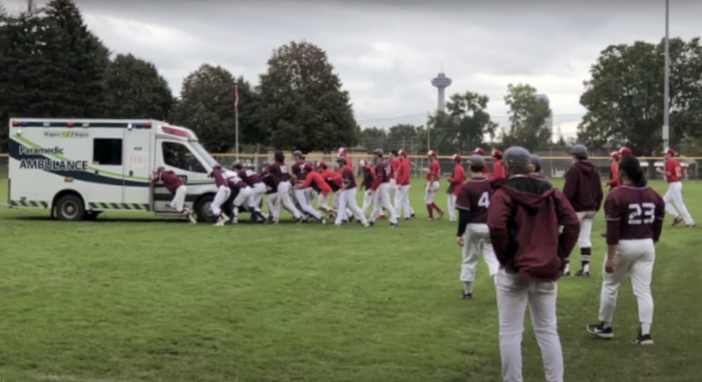 Gryphons and Marauders players help push an ambulance out of the mud