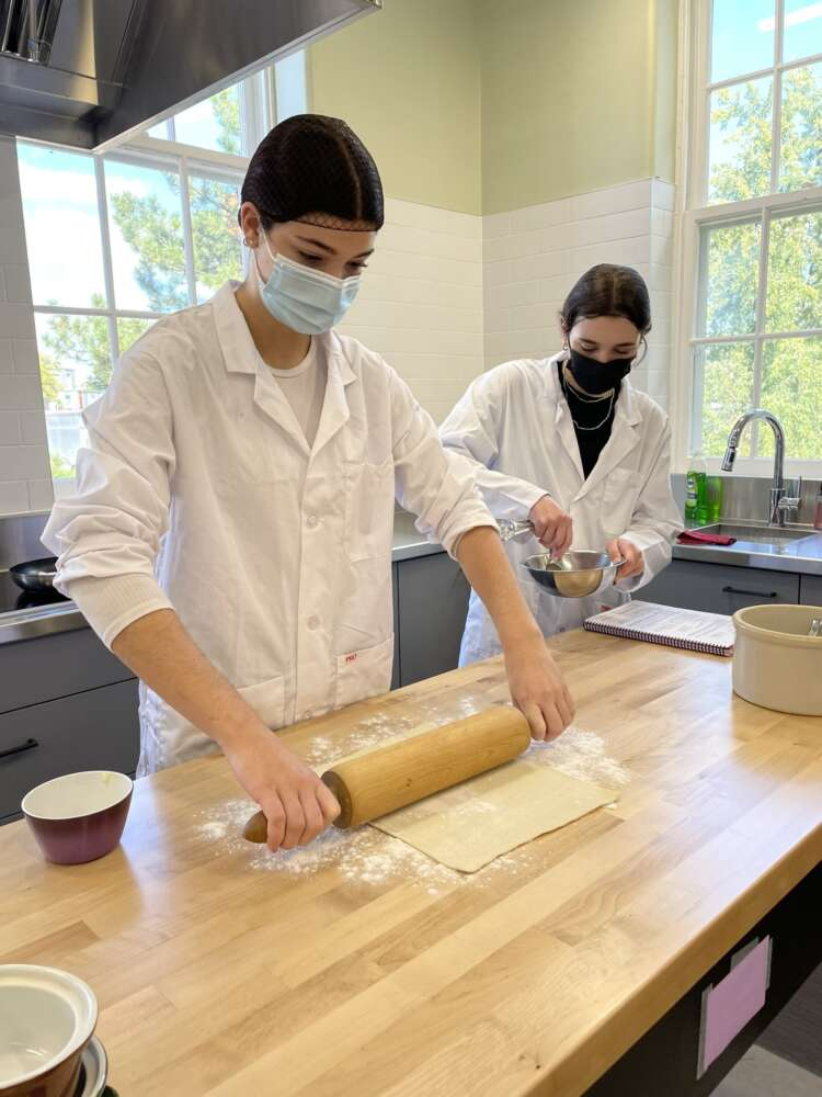 Students wearing lab coats rollout dough